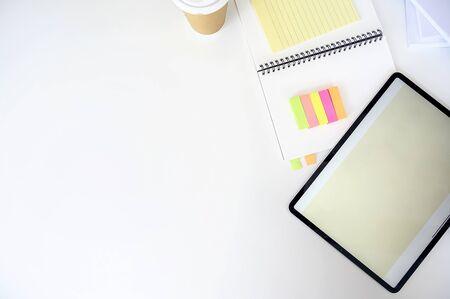 Top view tablet with blank screen, notebook and sticky note on white background, copy space.