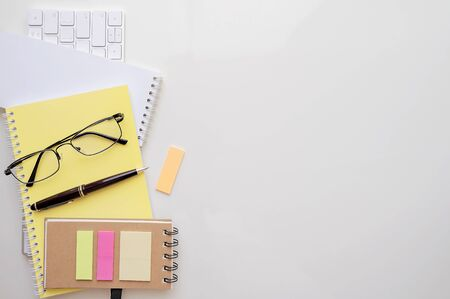 mockup notebook, white keyboard, glasses, pen and sticky note on white background, top view and copy space. Stock fotó