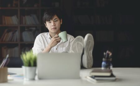 Portrait of young man holding cup and sitting at desk office, put his foot on the table and thinking about his job.