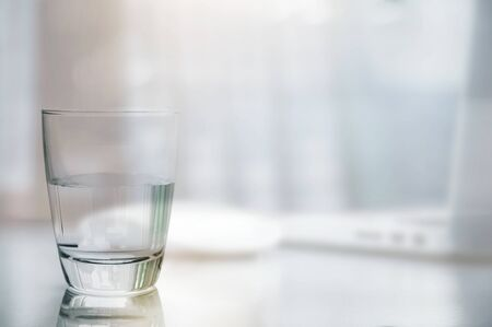 Closeup glass of clean water on white table with blurred image of laptop and mouse background, copy space. Фото со стока