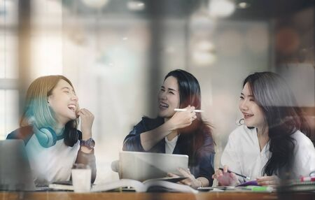 Women having fun while working together at cafe, laughing and enjoying while working. Looking through window glass.
