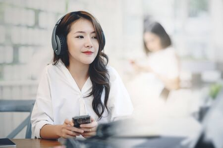 Young woman listening music with headphone while sitting at cafe.