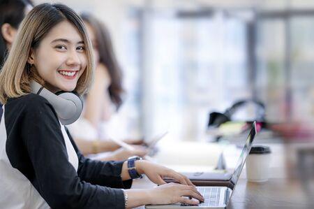 Portret van een jonge vrouw die lacht en naar de camera kijkt terwijl ze met haar vrienden in een modern kantoor werkt.