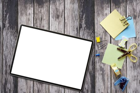 Mockup tablet with blank screen with supplies on old wooden table background, copy space, top view.