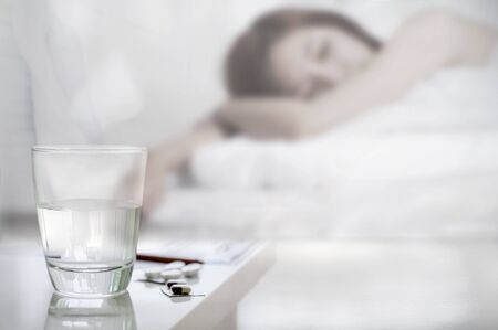 Closeup glass of water and pills with suffering sick woman in bed, copy space