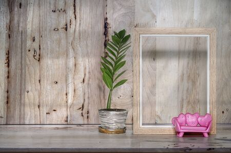 Mockup blank wooden picture frame and houseplant on plank wooden table background. Copy space for product display. Archivio Fotografico