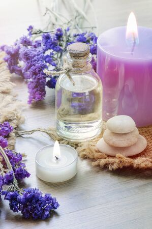 Bottle with lavender essential oil , candle on wooden table. Body care  and spa concept. Vertical view.