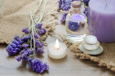 Bottle with lavender essential oil , candle on wooden table. Body care  and spa concept.