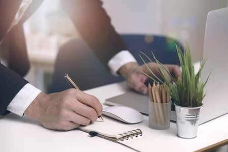 Closeup shot of businessman writing on notebook with pen while standing at office desk in modern office.
