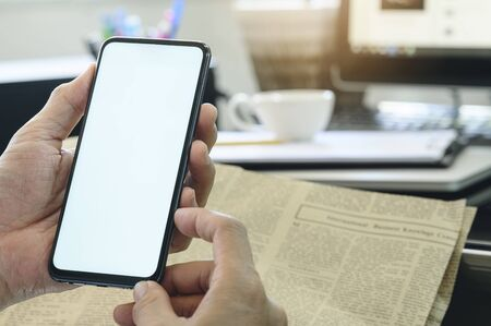 Closeup man using smartphone at  office. Blank screen for graphics display montage. Standard-Bild