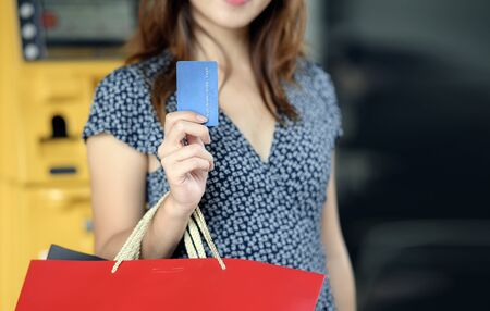 Closeup woman with shopping bags holding blue credit card and showing, copy space. 免版税图像
