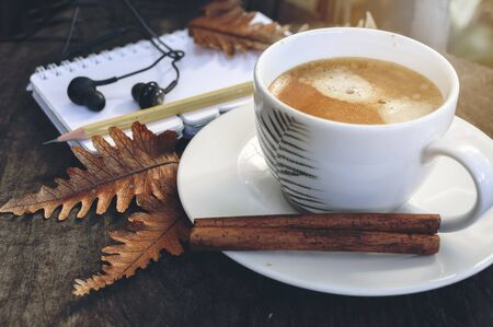 Top view cup of coffee with earphone, pencil, diary and dry leaf and earphone on wooden background, copy space. Standard-Bild