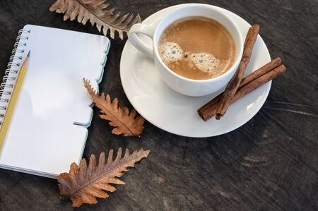 Top view cup of coffee with notebook and dry leaf on wooden background, copy space.