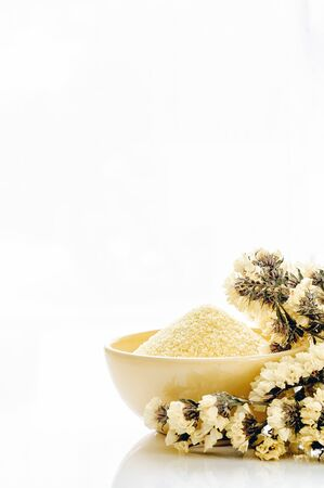 vertical view yellow cup of yellow scrub powder wiht yellow flower on white background, copy spacd for text. Spa and beauty concept. Archivio Fotografico