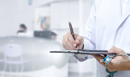 Cropped image of doctor hand writing on application form while standing at hospital. Copy space. Archivio Fotografico