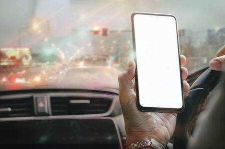 Shot of man holding smartphone with blank screen while sitting in car and struck on traffic jam.