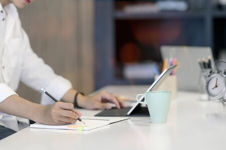 Cropped shot of man writing on notebook with pencil while sitting at office desk.