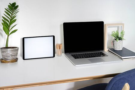 Mockup laptop and tablet with blank screen on white top table. Standard-Bild
