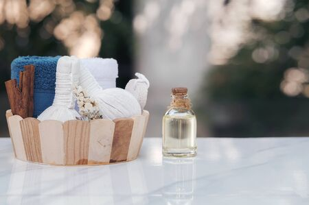 Spa treatments set in wooden bucket with herbal compressing ball, oil bottle, candles and towel on marble top table. Beauty and body care concept.