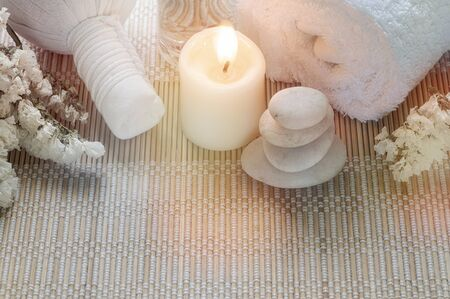 Spa treatments set with herbal compressing ball, oil bottle, candles and towel on bamboo plate background - Beauty and body care concept