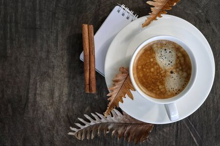 Top view cup of coffee with dry leaf on wooden background, copy space. Standard-Bild