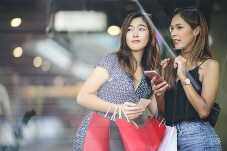 Two attractive asian women talking together and using smartphone while shopping at the mall, looking through window glass. Copy space.