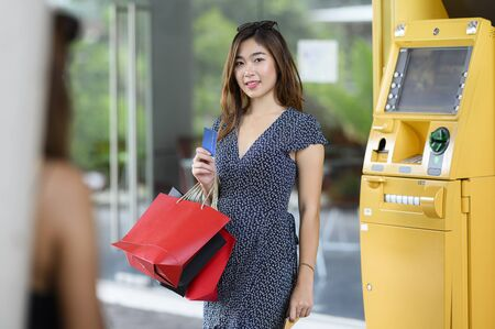 Portrait of beautiful asian woman with shopping bags and holding credit card standing near yellow ATM. Looking at camera. Standard-Bild