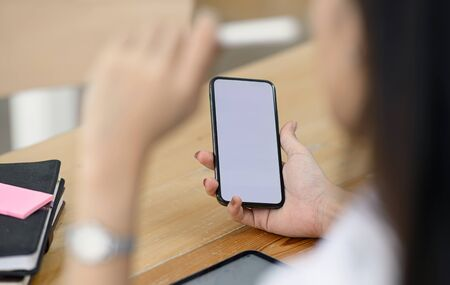Closeup female hand holding smartphone with blank screen for graphics display montage.