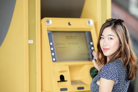 Portrait of beautiful asian woman withdrawing the case from ATM machine.