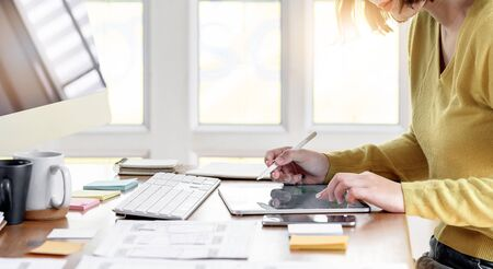 Young woman working with tablet for new project while sitting at modern office.