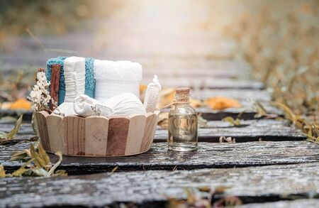 Spa treatments set in wooden bucket with herbal compressing ball, oil bottle, candles and towel on wet nature background - Beauty and body care concept.