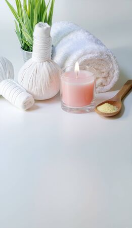 Spa treatments set with spoon of salt, herbal compressing ball, candles and towel on white background - Beauty concept, vertical view.