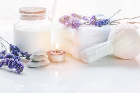 Spa treatments set with herbal compressing ball, oil bottle, candles and towel on wooden background - Beauty and body care concept