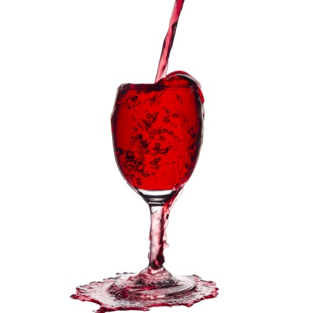 over flow pouring red wine isolated on white background Standard-Bild