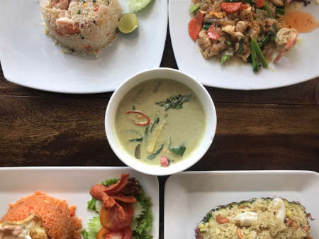 Top view of five type of Thai dishes served on a table. Seafood fried rice, seafood fried noodle, green curry soup, Tomyam fried rice and Thai seafood pineapple rice. Stock Photo