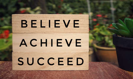 Motivational and inspirational quote - 'BELIEVE, ACHIEVE, SUCCEED' written on wooden blocks. Blurred styled background. Archivio Fotografico
