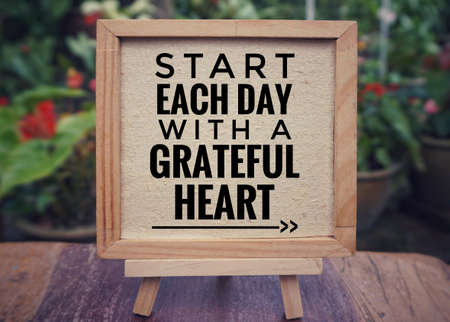 Motivational and inspirational quote - a€?Start each day with a grateful hearta€? written on a framed white paper. Vintage styled background.