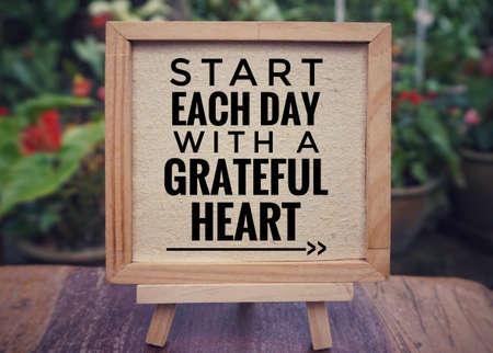 """Motivierendes und inspirierendes Zitat - """"Beginnen Sie jeden Tag mit einem dankbaren Herzen"""", geschrieben auf einem gerahmten Weißbuch. Weinlese gestylter Hintergrund. Standard-Bild"""