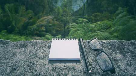 Conceptual  - A notepad, pen and eyeglasses on a concrete table with nature background.