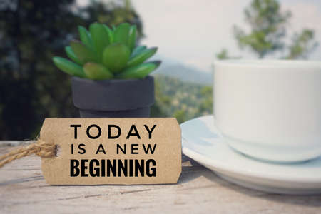 Motivational and inspirational quote - 'TODAY IS A NEW BEGINNING' written on a paper tag. Blurred styled background. Banco de Imagens
