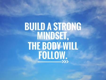 Motivational and inspirational quote - 'Building a strong mindset, the body will follow '. Background of blurred sky.
