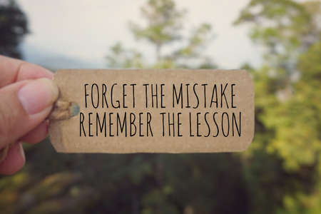 Motivational and inspirational quote - 'Forget the mistake, remember the lesson' written on a paper tag. Vintage styled background.
