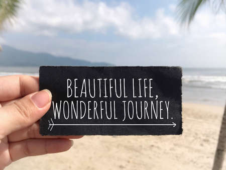 Motivational and inspirational quote - 'Beautiful life, wonderful journey.' written on a black paper. Blurred styled background.