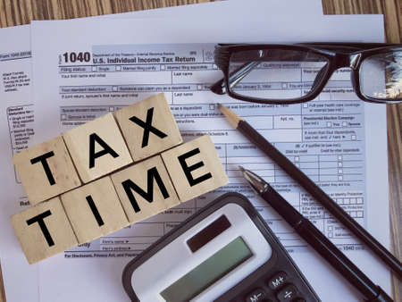 United States federal income tax return IRS 1040 documents, with pen, pencil, calculator,eyeglasses and wooden blocks with 'TAX TIME' written on them.