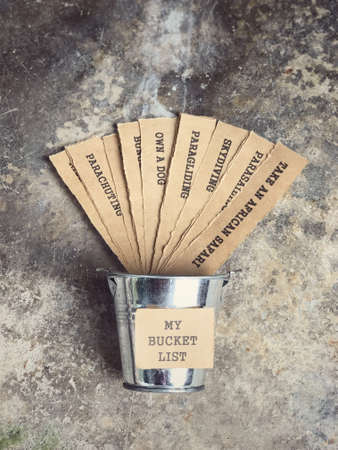 Motivational and inspirational concept - My Bucket List written on paper. There are list of wishes written on papers and placed inside the bucket. Vintage styled background.