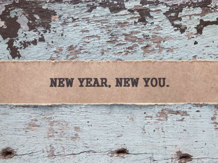 Motivational and inspirational quote - New, Year, New You written on a ripped paper.