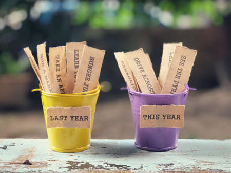New Year resolutions concept - Buckets of lists on a wooden table.