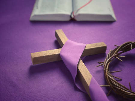 Good Friday, Lent Season and Holy Week concept - A religious cross, a bible and a woven crown of thorns on purple background.