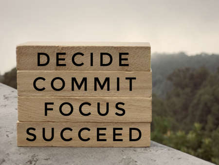 Motivational and inspirational words - Decide, Commit, Focus,Succeed written on wooden rectangular blocks.