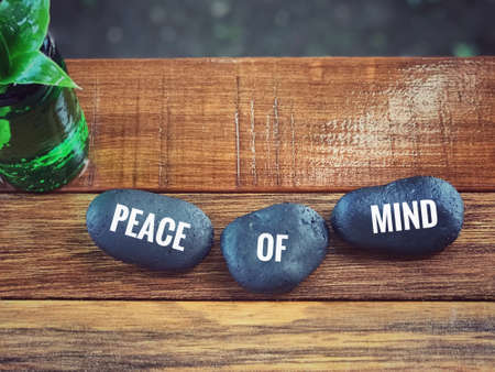 Inspirational wording - Peace of Mind written on pebbles. Blurred styled background.